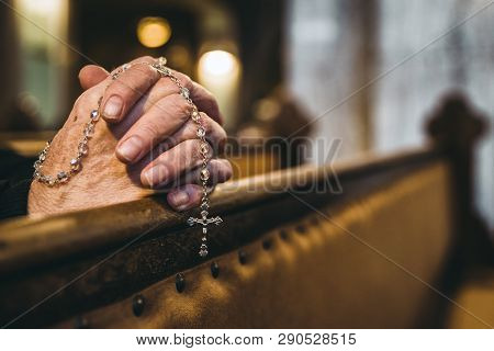 Praying Senior Hands With Rosary In Church Bench