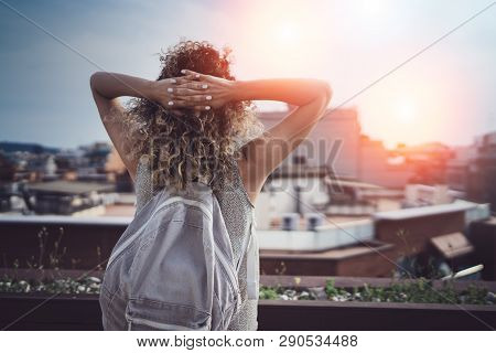 Hansome Young Woman Curly Hair And Casual Wear Enjoing Beautiful View Of The City On Sunset.