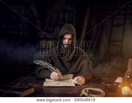 Medieval monk in robe writes with a goose feather