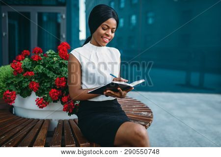 Businesswoman writes in notepad in front of office