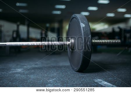 Barbell on the floor in gym closeup view, nobody