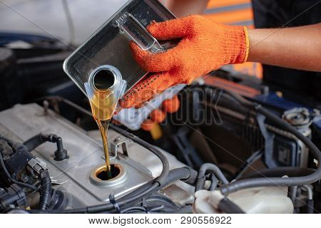 Mechanic Is Pouring Oil Into Engine. Car Hood Is Open. Change The Oil.