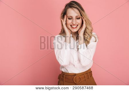 Portrait of joyful blond woman 30s in stylish outfit grabbing head in surprise isolated over red background poster