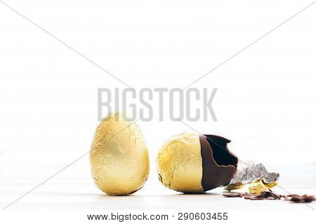 Stylish Easter Egg In Golden Foil And Broken Chocolate Egg With Chocolate Pieces In White Light With