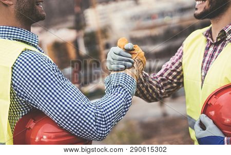 Young Builders Shaking Hands Making An Agreement On Construction Site - Workers Reaching A Deal And
