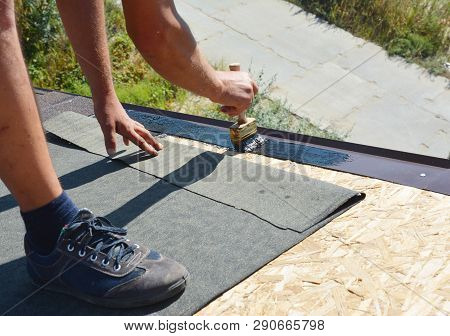 Roofer Contractor Gluing Waterproof Membrane On Wooden Roof Top Surface With Brush And Black Bitumen