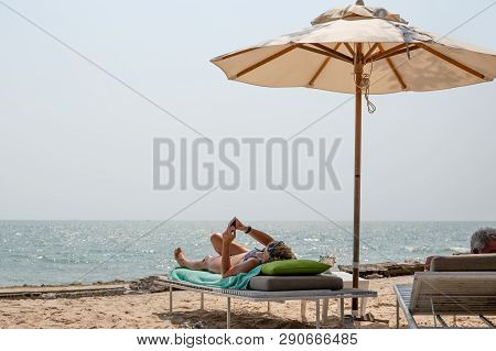 Retried Couple Lying On Deckchairs Using Cell Phone On The Beach.
