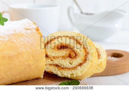 Delicious Biscuit Roll With Apricot Jam And A Cup Of Tea On A White Wooden Table. Dessert For Breakf