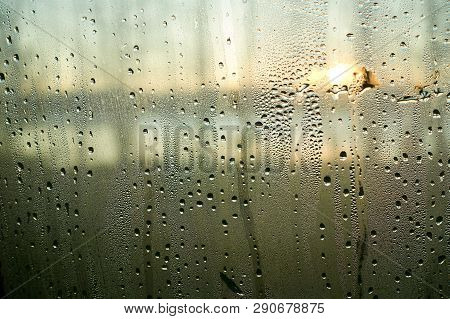 Raining Water Drops On A Wet Window Closeup Image. Condensed Moisture On A Glass Surface In The Morn