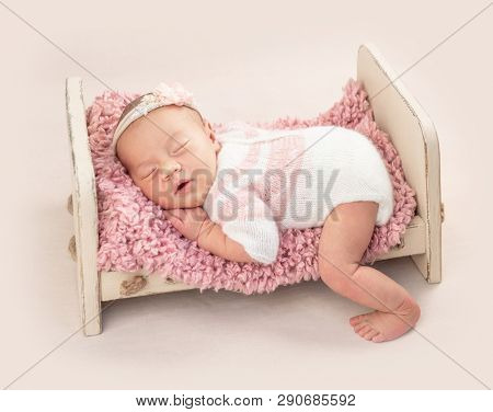 Little cutie infant in neatly knitted bodysuit on baby bed, isolated on white background