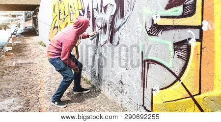 Street Artist Painting Colorful Graffiti On Public Wall - Modern Art Concept With Urban Guy Performi