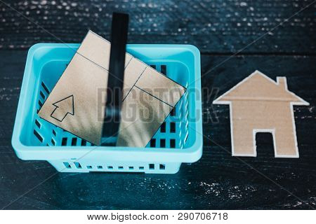 Shopping Basket With Parcel And Small Cardboard House Next To It
