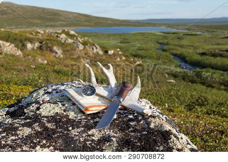 Knife, compass and topographyc map on the rock. Hiking equipment. Beautiful lake and mountains on background. poster