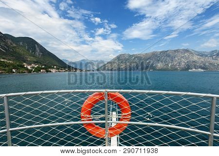 Tourist Ship Approaching Bay On Clear Summer Day - View From Upper Deck With The Bulwark And Life Bu