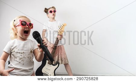 Two Girls In Pink Sunglasses And Identical T-shirts Sing With A Microphone And Play The Electric Gui