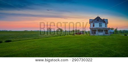 Abandoned Old Farm House At Dusk With Colorful Sky.