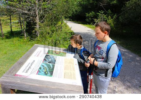 Young Hikers Observe A Sign Of The Park On The Path Along The Lake, Lago Di Dobbiaco, Dolomites, Ita