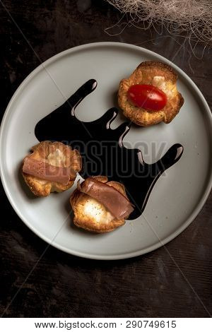 Few Puff Pastry Cups Filled By Cheese And Ham On Blue Plate With Dark Sauce