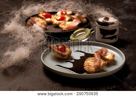 Horizontal Photo Of Blue Plate With Puff Pastry Cups. Cups Are Stuffed By Melted Cheese. Ham And Red