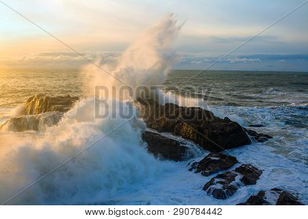 Seascape. Waves Of The Atlantic Ocean Crashing Against A Rock At Sunset. Portugal