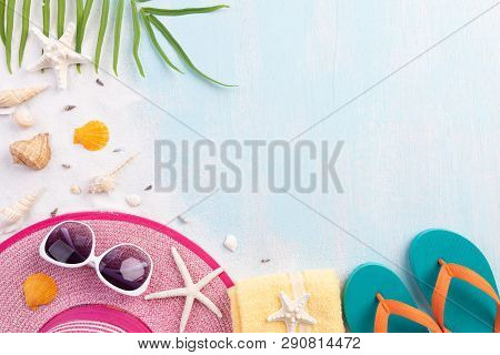 Beach Accessories Including Flip Flop, Starfish, Beach Hat And Sea Shell On Sandy Beach And Blue Woo