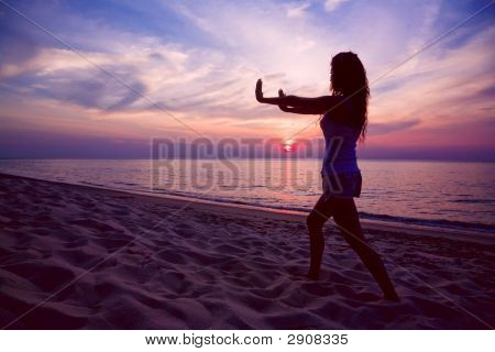Woman Doing Yoga On Sunset Beach