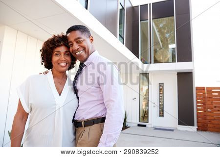 Middle aged black couple stand outside looking to camera in front of their modern home, close up