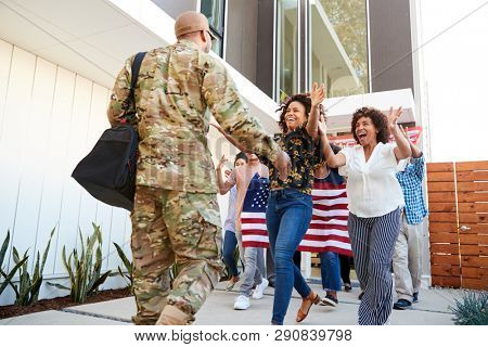 Family welcoming back millennial black soldier   returning home,low angle view