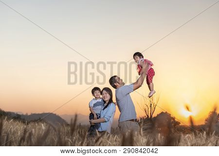Family Having Fun And Playing In A Barley Field In Summer At Sunset Time.