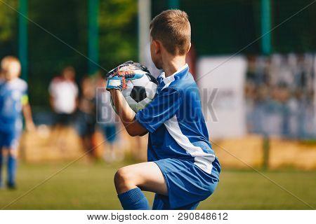 Young Soccer Goalie Goalkeeper Catching Ball. Young Boy Soccer Goalie. Soccer Game On Sunny Summer D