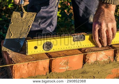 Bricklayer checks the horizontal level of brick masonry wall with a bubble level and and lacing cord. Bubble centered. poster