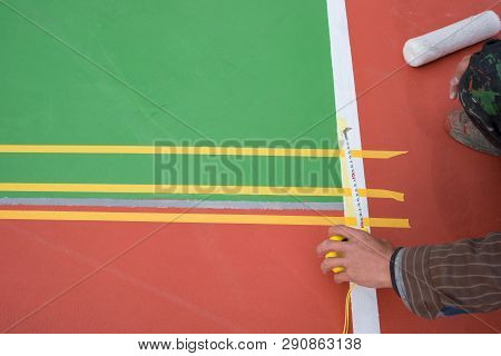 Worker Measuring And Marking The Sideline On The Floor For An Outdoor Stadium