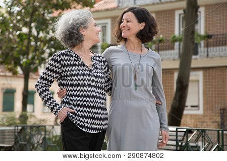 Cheerful Smiling Mother And Daughter Walking Around Uptown Old District. Young And Senior Women Hugg