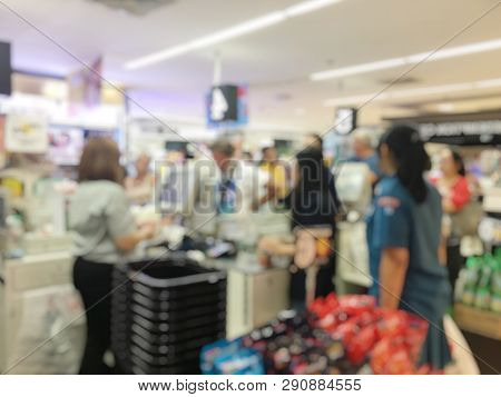 Blurred Image Of Cashier With Long Line Of People At Check-out Counter Of Supermarket. Customers Pay