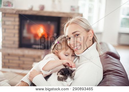 Beautiful Mother, Little Daughter And A Cat Are Sitting On The Sofa Near The Fireplace. Family In Th