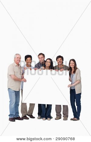 Smiling group of friends holding blank sign together against a white background