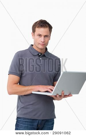 Young man standing with his laptop against a white background