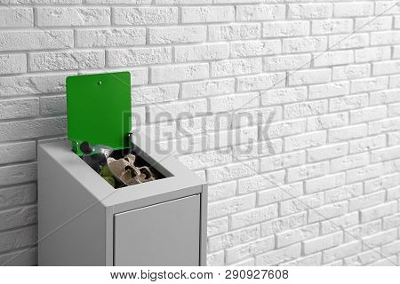 Overfilled Trash Bin Near Brick Wall, Space For Text. Recycling Concept