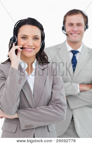 Smiling call center agents with headsets on and arms folded against a white background poster