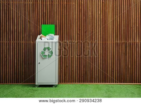 Overfilled Trash Bin With Recycling Symbol Near Wooden Wall Indoors. Space For Text