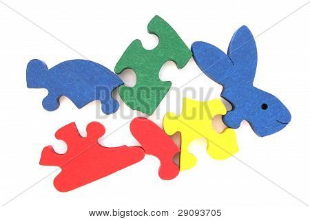 Colorful wooden rabbit puzzle toy partially scattered