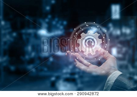 A Closeup Of A Businessman Hand Holding An Update Cogwheel Inside A Digital Networking Sphere. The C