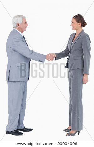 Side view of smiling businesspartner shaking hands against a white background
