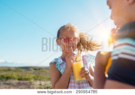 Portrait of little girl drinking orange juice in a glass with straw. Rear view of brother drinking with sister at outdoor park. Boy and cute girl with sunglasses suck from the straw a fresh juice.