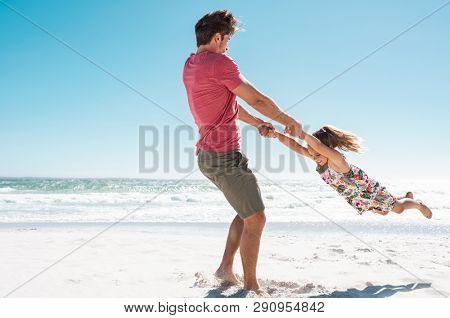 Father and daughter playing together on the beach with copy space. Happy dad and cute smiling little girl playing at seaside. Young daughter having fun at beach with ring around the rosie.