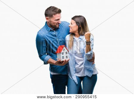 Young couple in love holding house over isolated background annoyed and frustrated shouting with anger, crazy and yelling with raised hand, anger concept