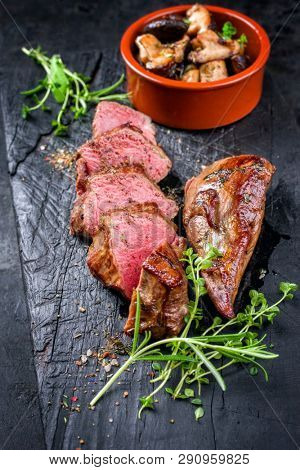 Traditional barbecue aged sliced venison sirloin with mushroom and herbs as closeup on a carbonized old board
