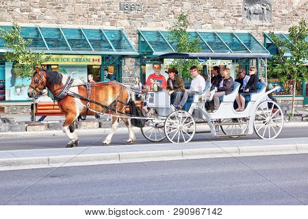 Banff, Canada - July 3, 2011: Tourists On A Horse Drawn Carriage Ride Through Banff Avenue In The Ca