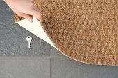 Young woman revealing hidden key under door mat, top view with space for text poster