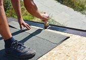Roofer contractor gluing waterproof membrane on wooden roof top surface with brush and black bitumen  spray on tar before installing asphalt shingles. poster
